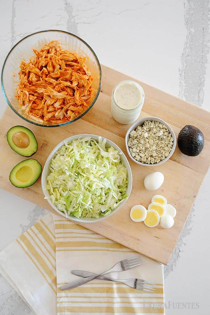 Image: ingredients laid out for buffalo chicken salad. Including, shredded chicken, a halved avocado, sliced hard boiled eggs, a bowl of blue cheese chunks and a jar of ranch dressing.