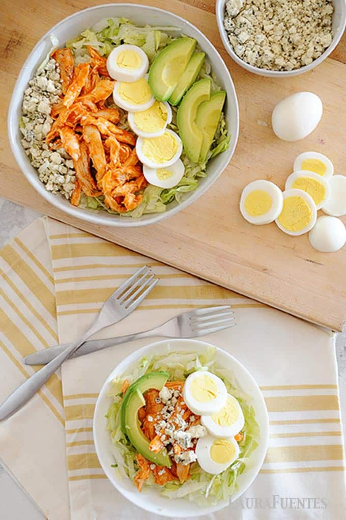 image: Large serving bowl of buffalo chicken salad with smaller bowl of the salad and two forks