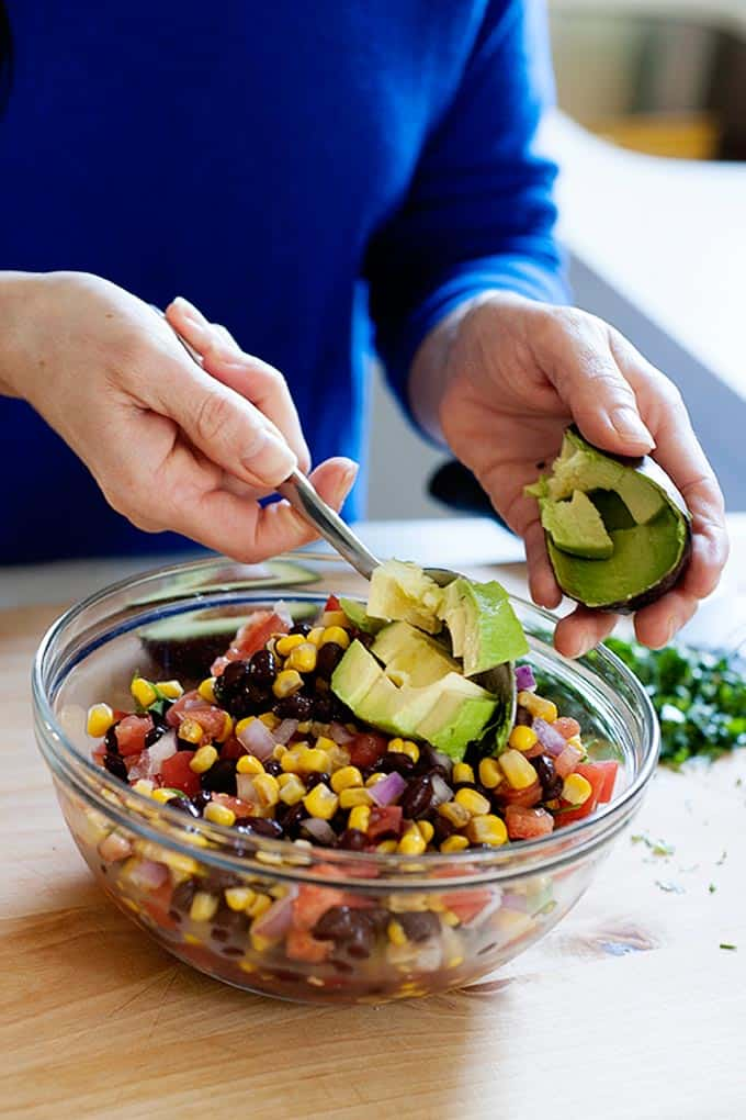 corn and avocado salsa mixing in a bowl