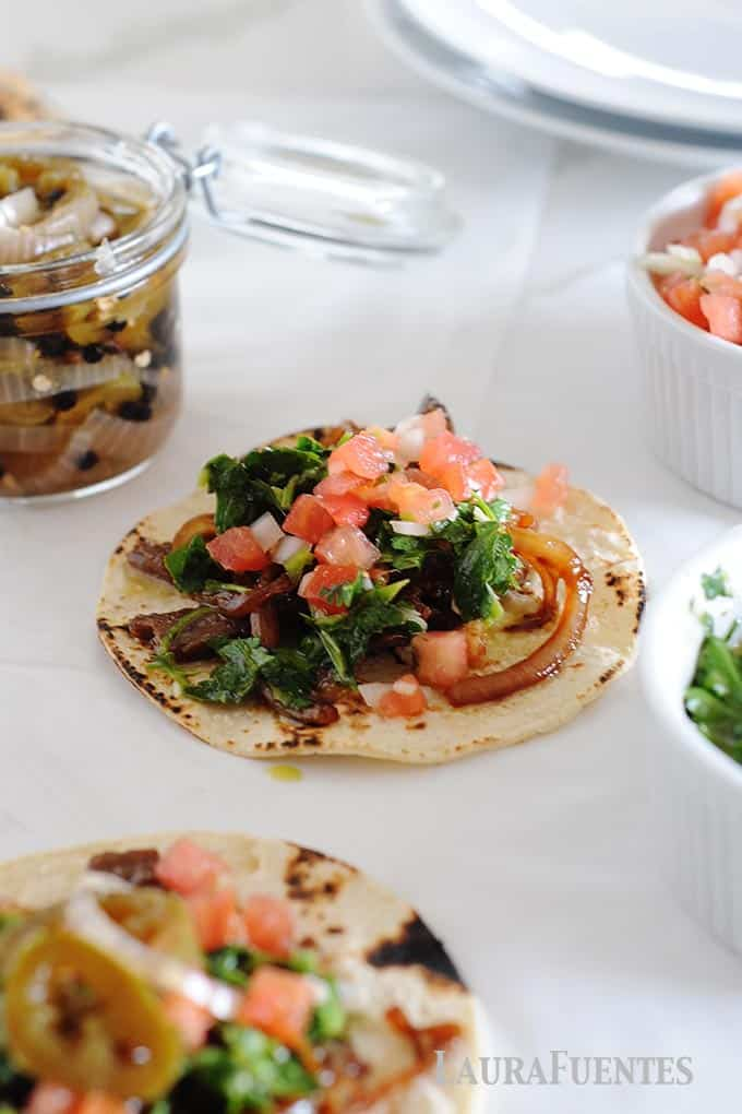 image: two steak tacos on a flat tortilla with grilled onions, pico de gallo and cilantro chimichurri