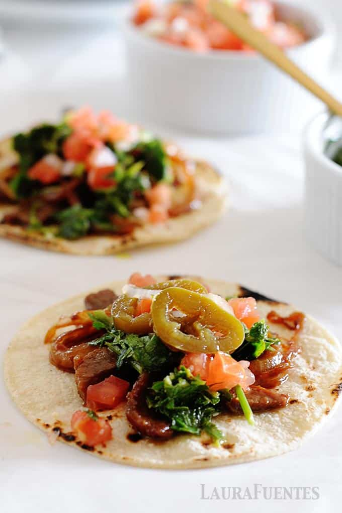 image: closeup on two steak tacos on a flat tortilla with grilled onions, pico de gallo and cilantro chimichurri
