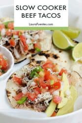 tacos on a plate with lime wedges - text reads slow cooker beef tacos