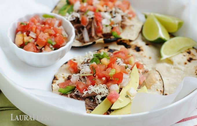 tacos in a dish with lime wedges