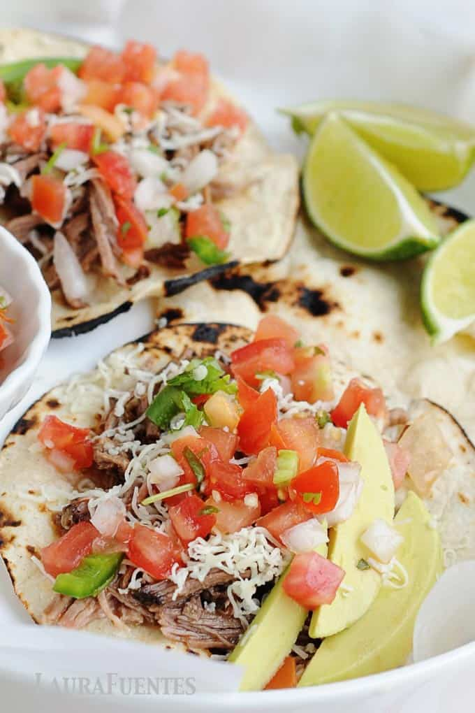 tacos with lime wedges, diced tomatoes and jalepenos