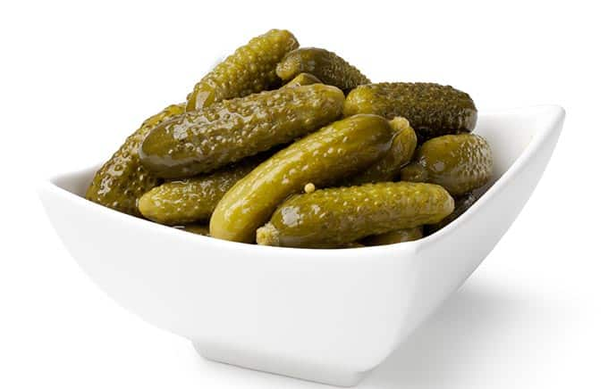 white bowl of whole pickles
