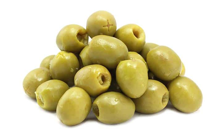 pile of green olives on white background