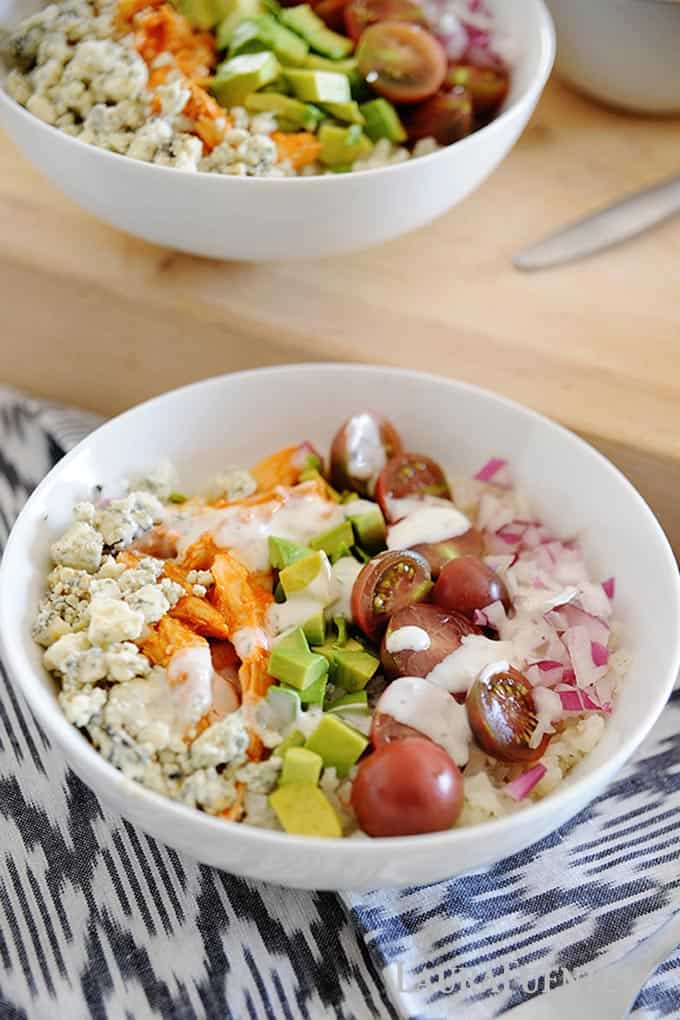 Image: salad bowl filled with rice, tomatoes, avocado slices, cheese crumbles and buffalo chicken with white ranch dressing on top.
