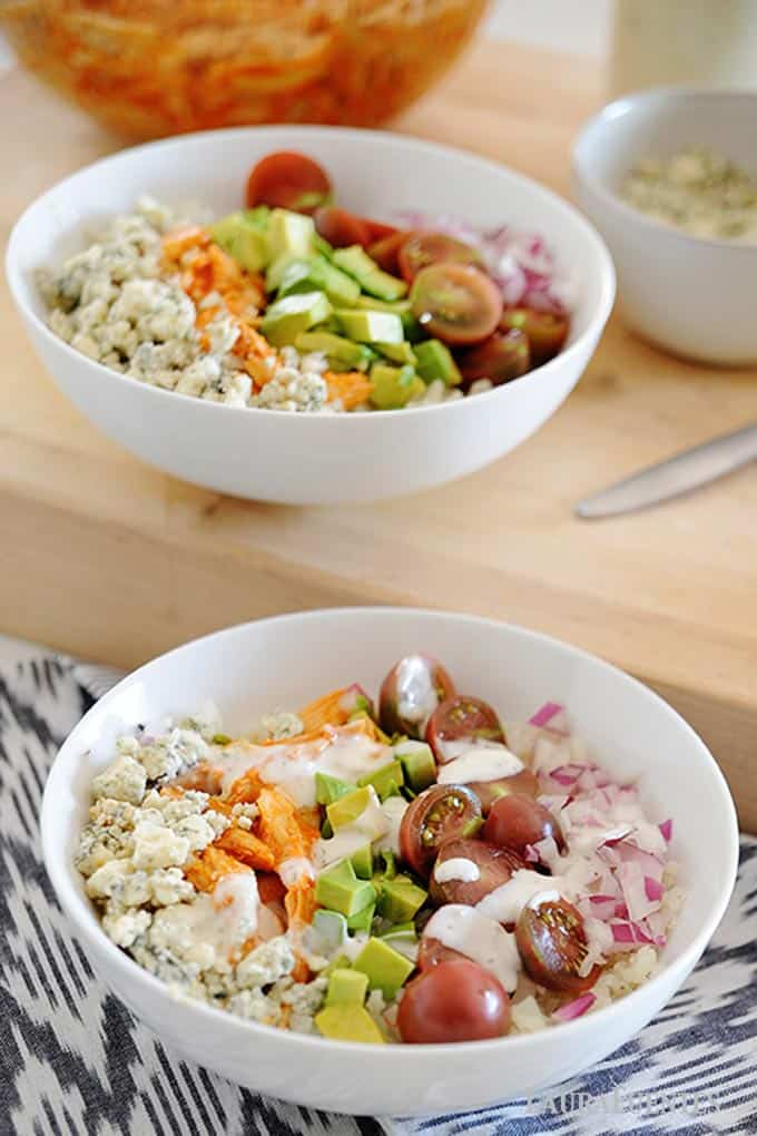 two white bowls of buffalo chicken, rice and vegetables