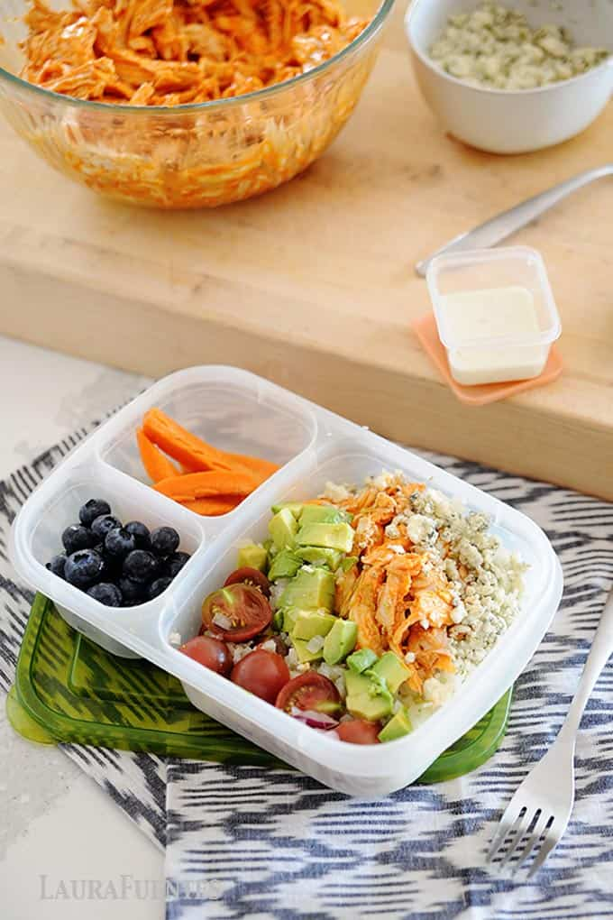 image: buffalo chicken, avocado cubes, halved tomatoes and cheese crumbles in a lunch container with carrot sticks and blueberries on the side.
