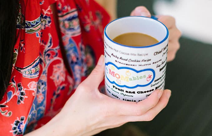 image: closeup on hands holding a white mug with the MOMables logo on it