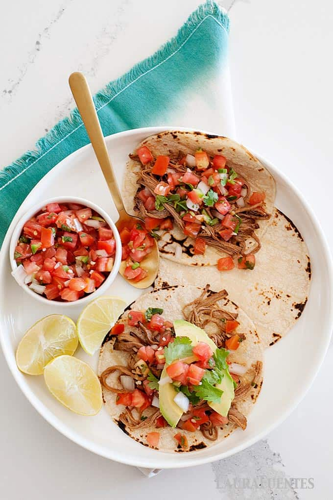 Plate of shredded tacos, fresh tomato salsa and lime wedges