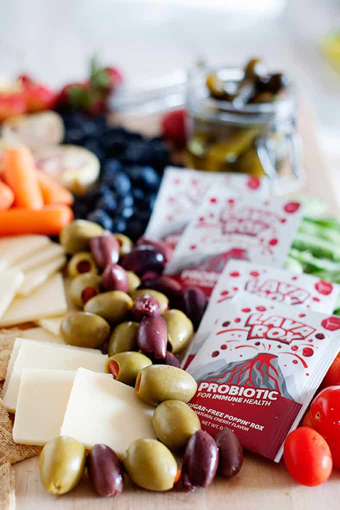 olives, sliced cheese, vegetables and probiotic supplements on a cutting board