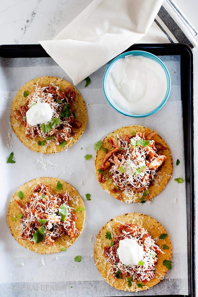4 tostadas on a sheet pan with a small bowl of sour cream