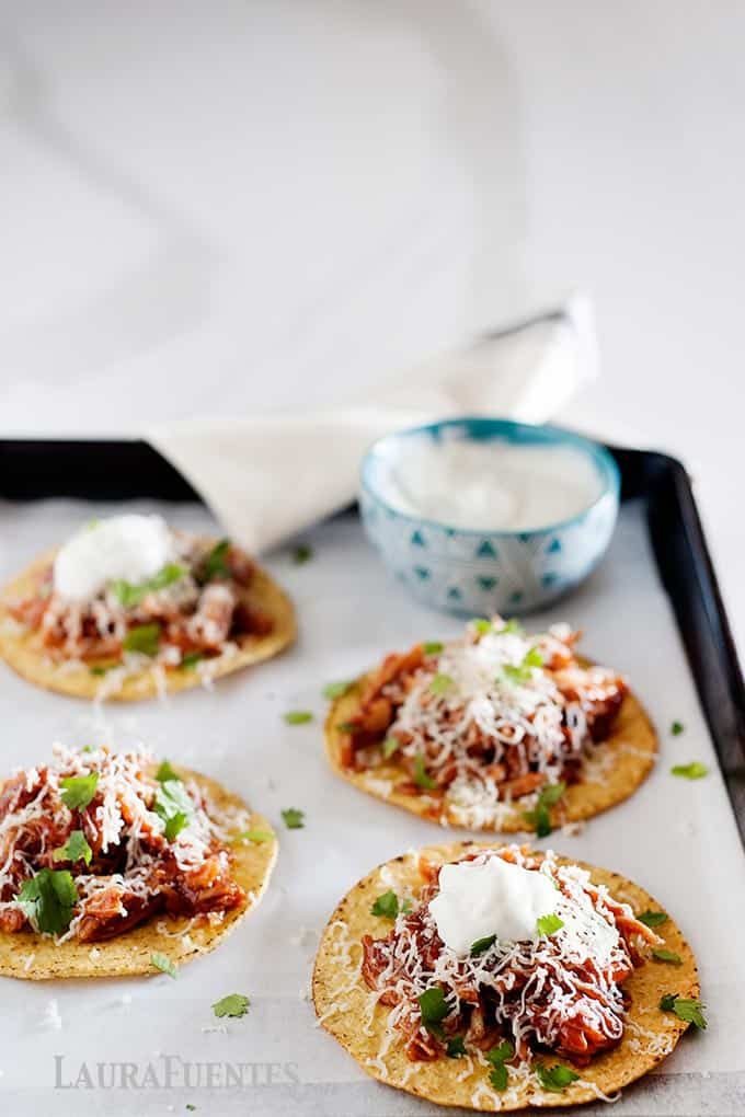 image: 4 tostadas on a sheet pan with a small bowl of sour cream - side shot image
