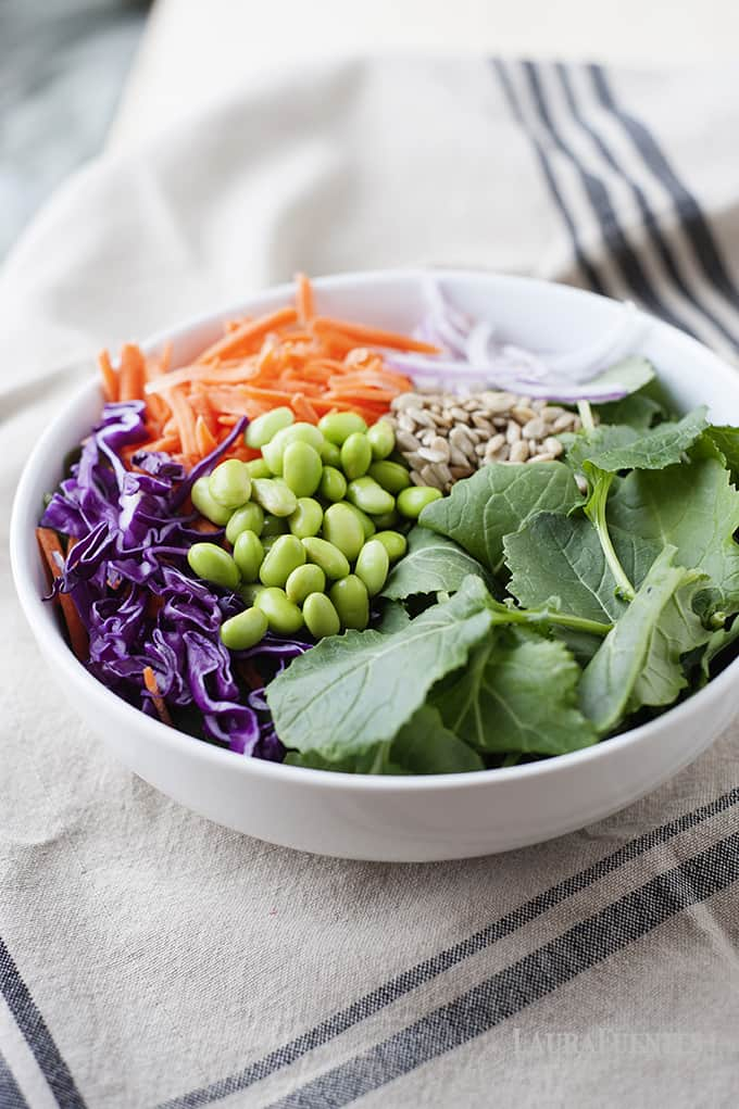 colorful salad with kale, edamame, carrots purple cabbage, seeds and onion slices