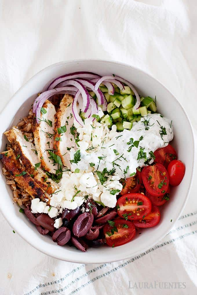 chicken, feta cheese, olives, cucumber, tomatoes and sauce all in a white bowl with farro