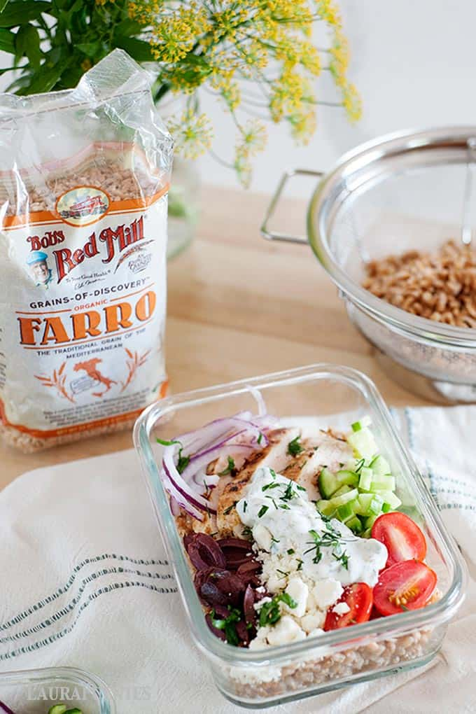 chicken farro recipe preppe in glass container with bag of extra farro in background