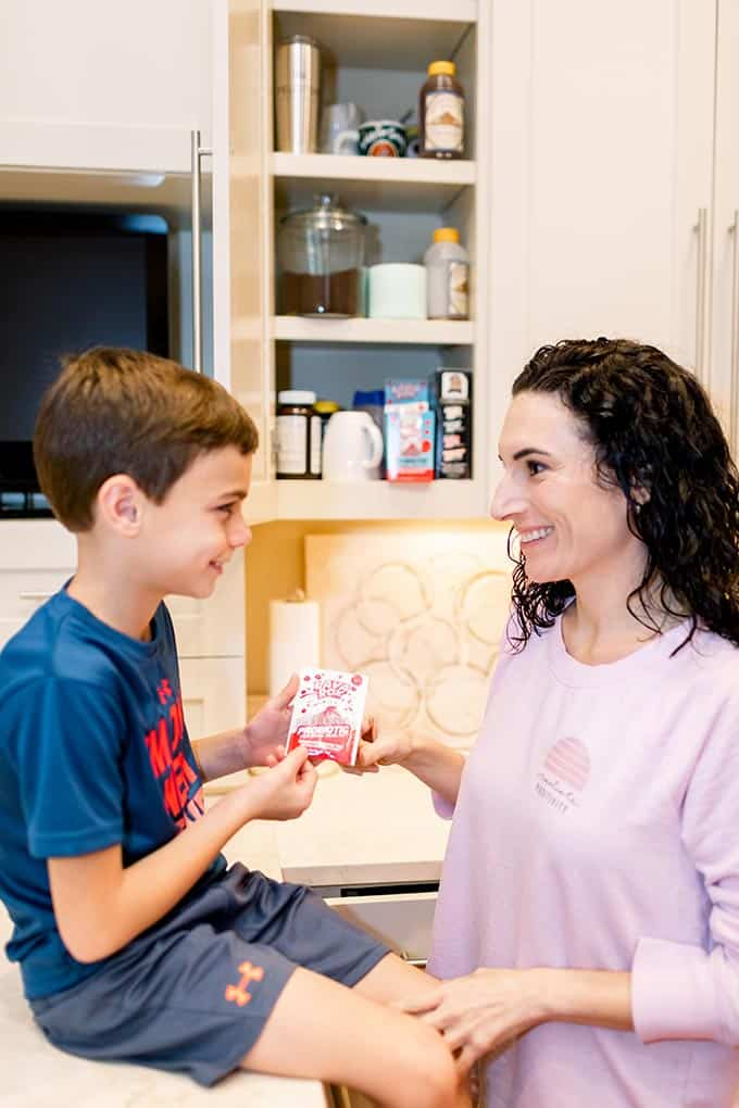 mom giving probiotics to smiling little boy