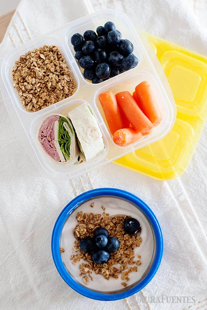 yogurt and sandwich rolls packed in a lunchbox with granola, carrots and blueberries