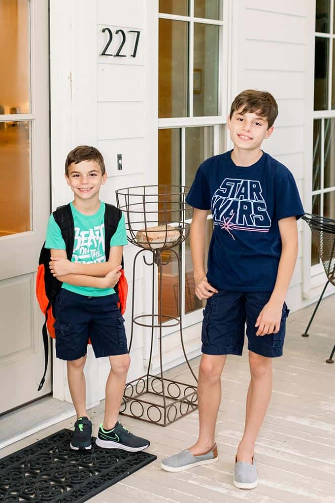 Two boys standing at door with backpacks ready for school.