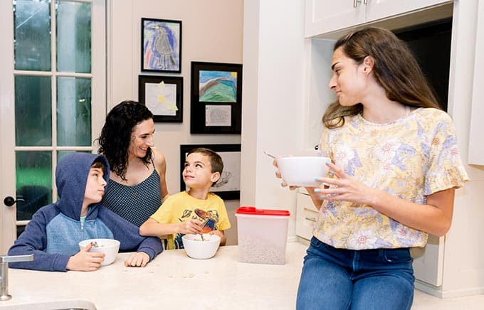 mom and three kids eating cereal in a kitchen