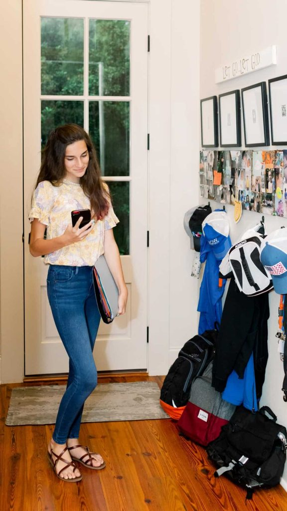 Tween girl in hallway with backpacks looking at phone.