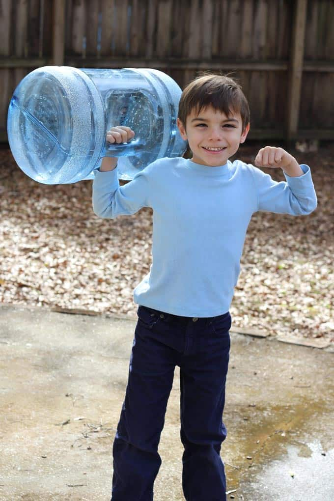 Image: little boy holding large empty water bottle flexing muscles and smiling.