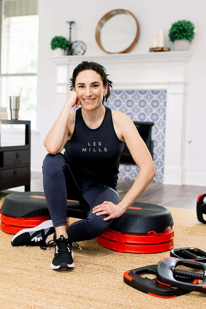 woman in les mills tank top sitting down before working out at home