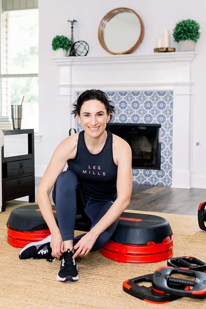 woman tying shoes before working out in living room