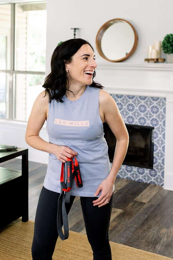 smiling woman holding workout gear in living room