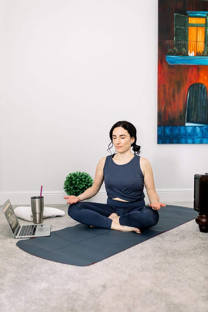 woman doing breathing exercises on a mat at home