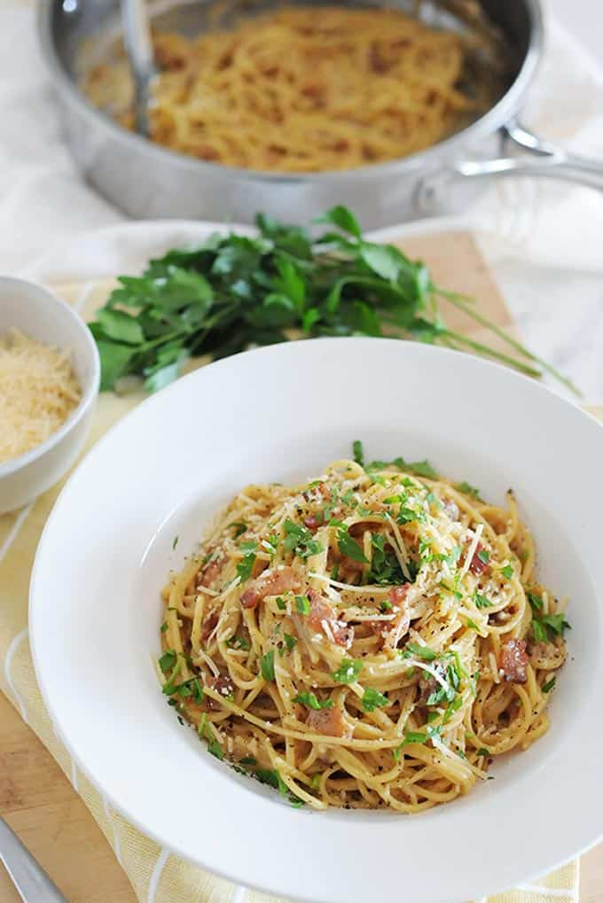 spaghetti carbonara in a bowl with pan of spaghetti in the background