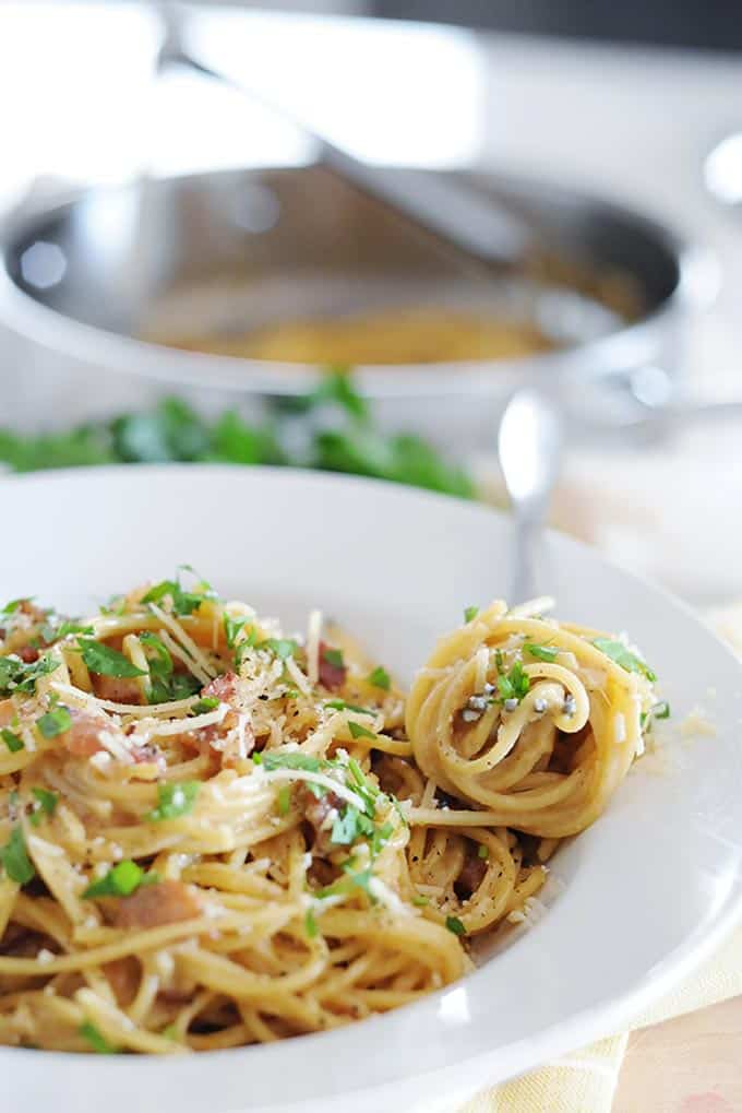 closeup of twirled carbonara spaghetti noodles with cooking pan and tons in background