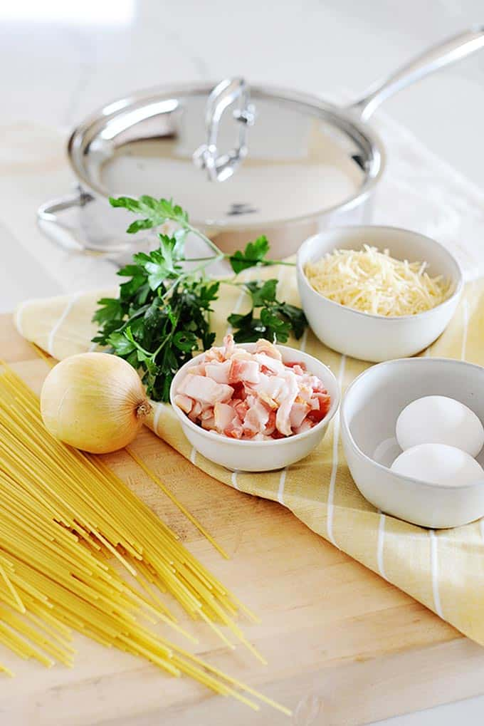 ingredients set out for carbanara sauce. Eggs, cheese, bacon, onion and dry noodles with cooking pan