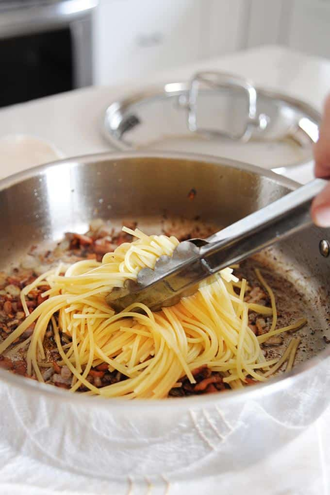 tongs placing cooked noodles into pan with browned bacon and onions