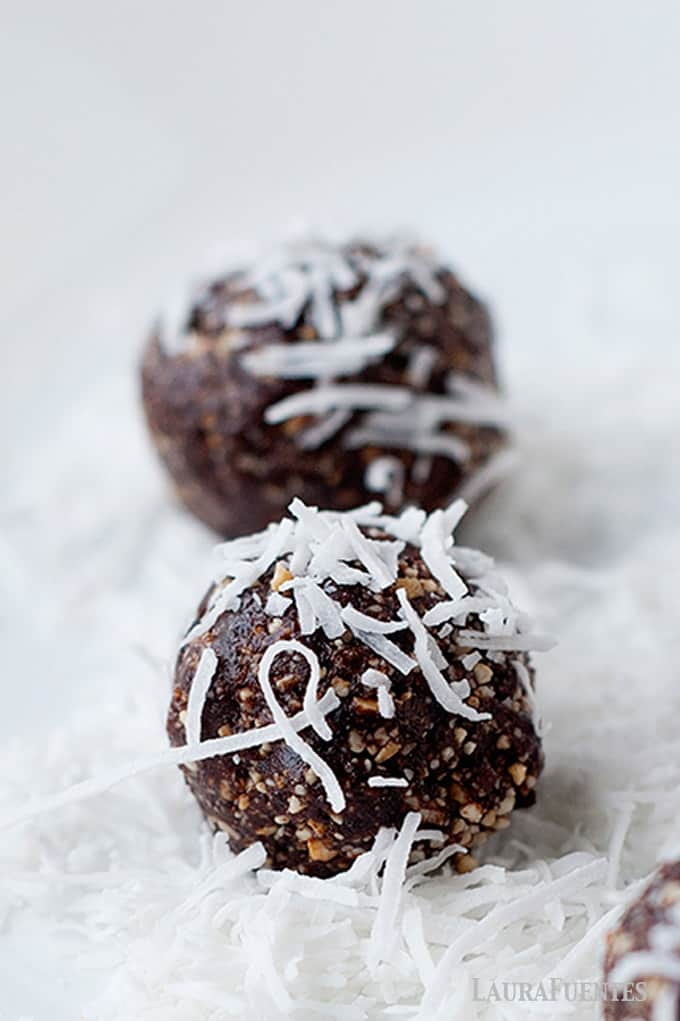 Two chocolate energy balls with coconut flakes on top of them