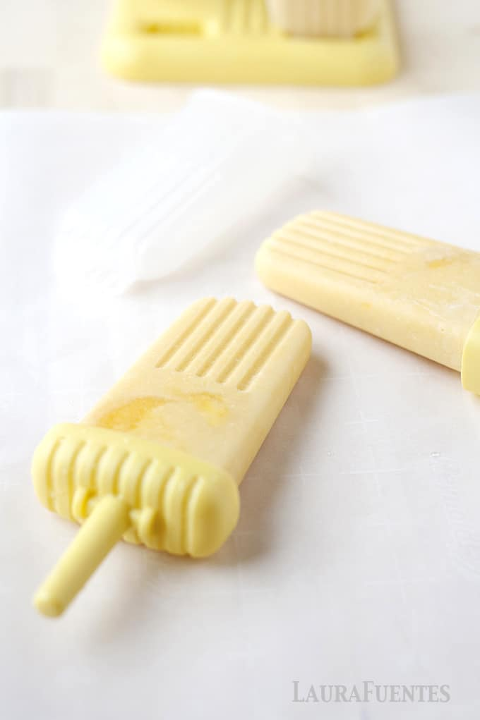 two homemade yellow mango popsicles on a white cloth