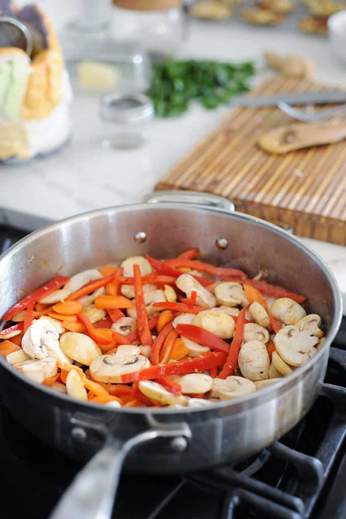 sliced mushrooms, red pepper and carrots in a skillet
