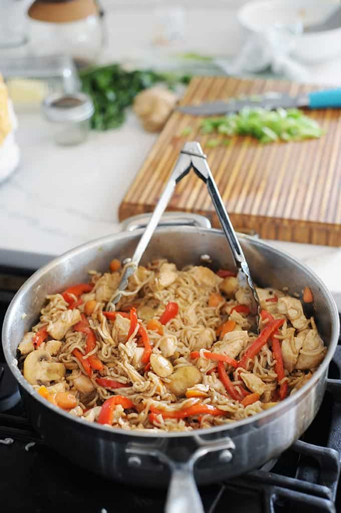 sliced mushrooms, red pepper and chicken in a skillet with thin ramen noodles