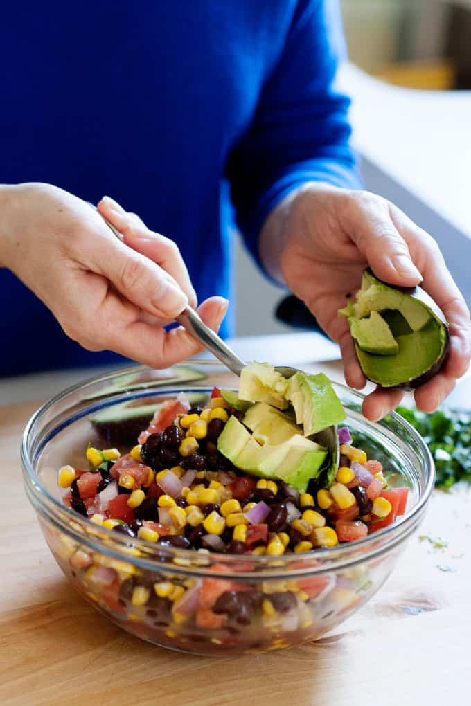 Spooning avocado pices into corn and bean salad