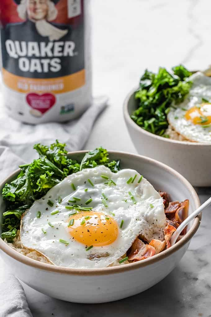 Bowl of oatmeal with sunny side up egg, bacon and green on top