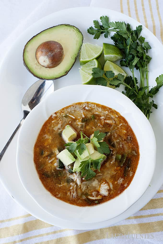 image: bowl of brown broth soup with avocado pieces on top