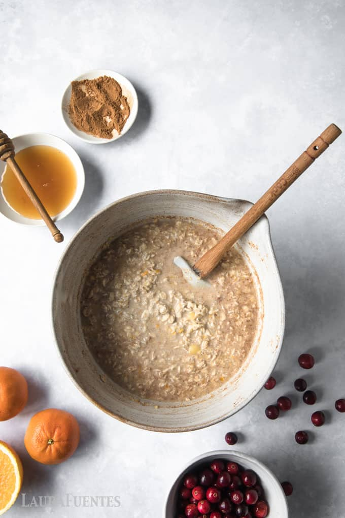 image: oats being stirred in large mixing bowl with oranges, honey and cranberries on the side of the image