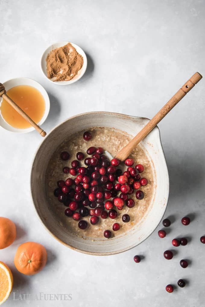 image: oatmeal in a large mixing bowl with cranberries poured on top. Other ingredients in photo: honey, oranges and cinnamon