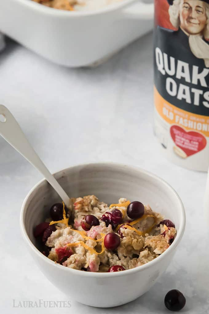 image: bowl of baked oatmeal with cranberries and orange zest on top