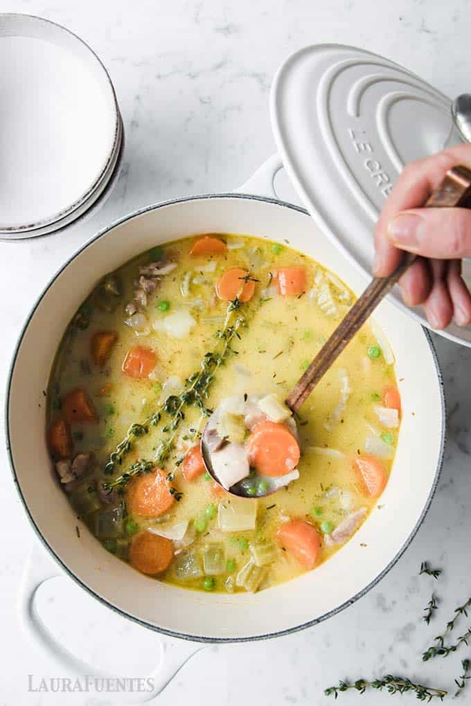 image: large bowl of chicken and vegetable soup with a ladle