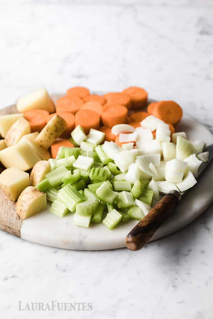 image: chopped onions, potatoes, carrots and celery