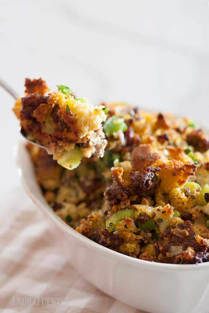 Image: dish of cornbread stuffing with spoon pulling out of it