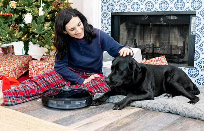 image: woman and black lab sitting by Christmas tree with ecovacs vacuum
