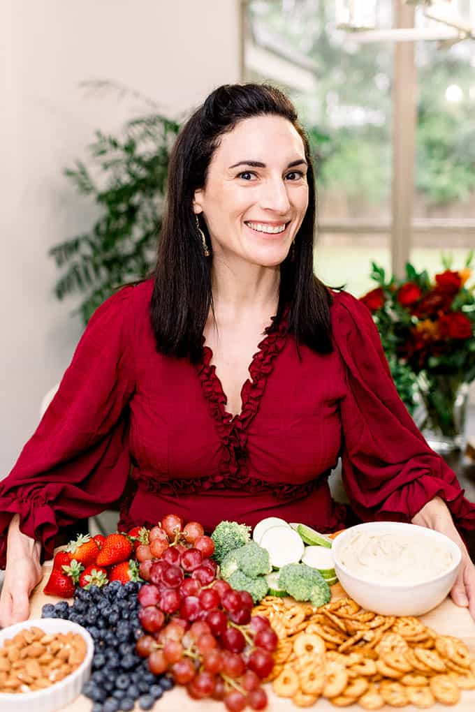 image: woman in red dress with platter of fruit and cheese